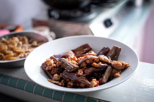 Hot spicy eggplant cooking with minced meat and chili served on ceramic plate.