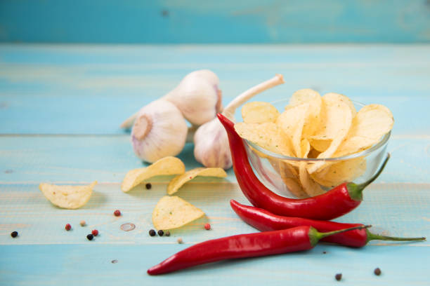 Hot Spicy Potato Chips Ready to Eat Potato chips in bowl on a wooden background, Salty crisps scattered on a table. Hot Spicy  Potato Chips Ready to Eat sriracha tiger zoo stock pictures, royalty-free photos & images