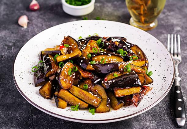 Heiße würzige Eintopf Aubergine im koreanischen Stil mit grünen Zwiebeln. Aubergine saute. Veganes Essen. – Foto