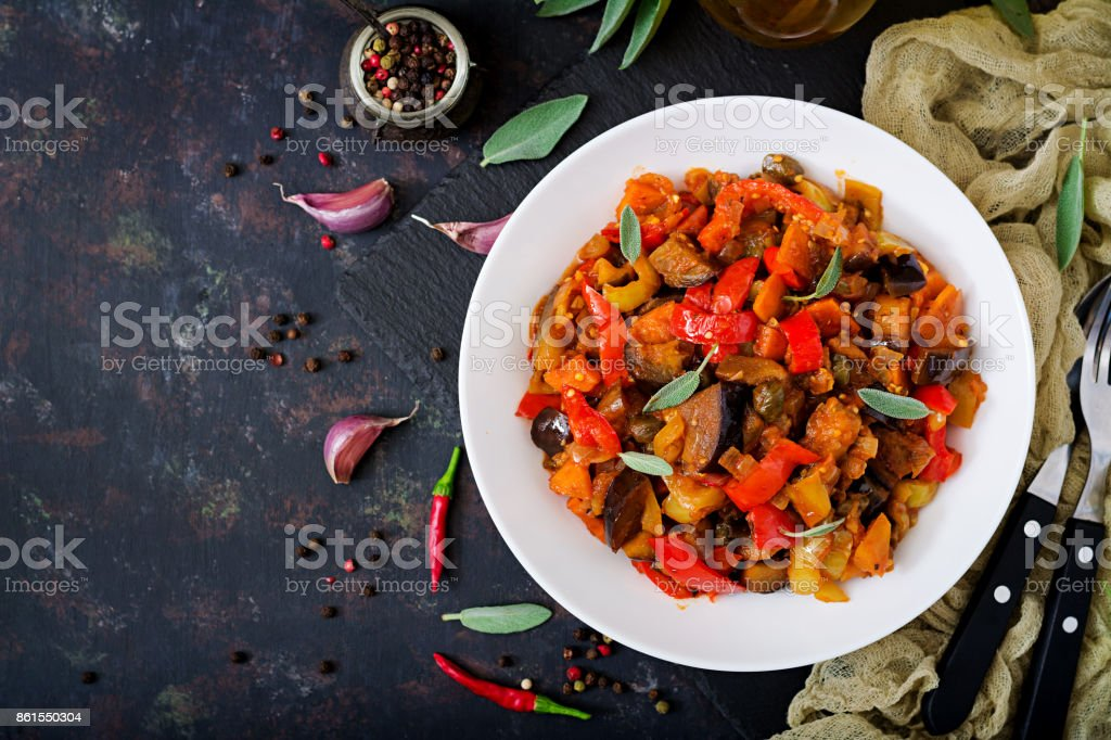 Hot spicy stew eggplant, sweet pepper, tomato and capers. Flat lay. Top view stock photo