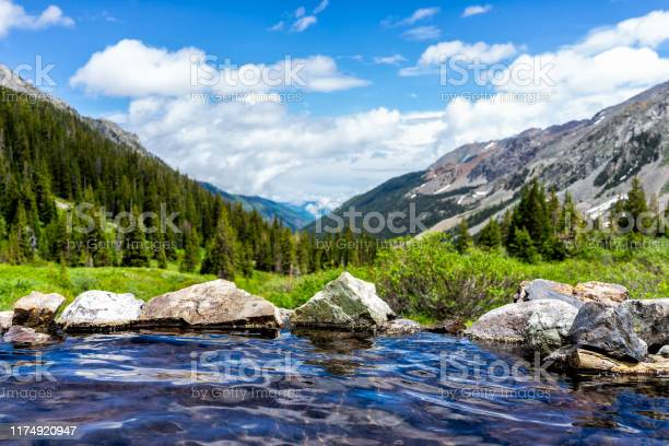Photo of Hot springs blue pool on Conundrum Creek Trail in Aspen, Colorado in 2019 summer with rocks stones and valley view with nobody
