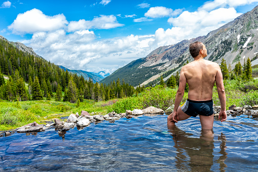 istock Hot springs water on Conundrum Creek Trail in Aspen, Colorado in 2019 summer with man in swimsuit looking at valley view 1174920875