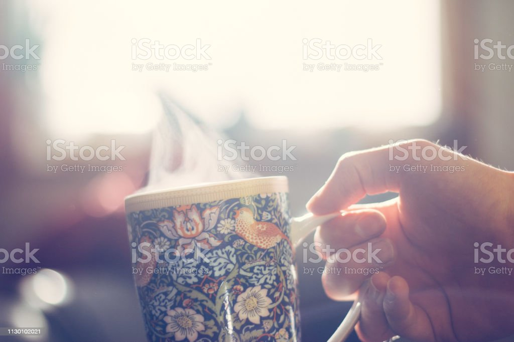 Man is holding a steaming tea cup in his hand for warm-up, sunlight,...