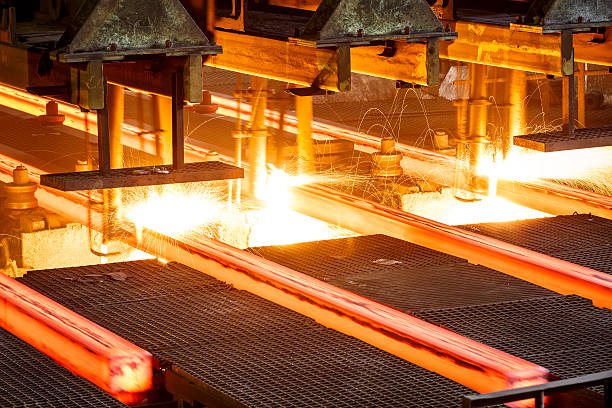 hot steel on conveyor in steel mill stock photo