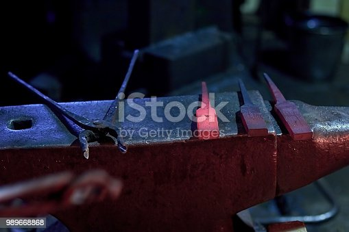 istock Hot steel parts and forge tongs on the anvil at the forge 989668868