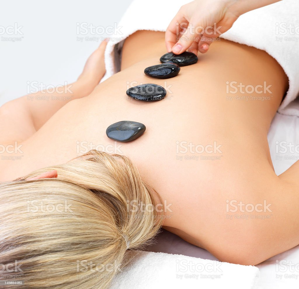 Hot stone massage of a young woman royalty-free stock photo