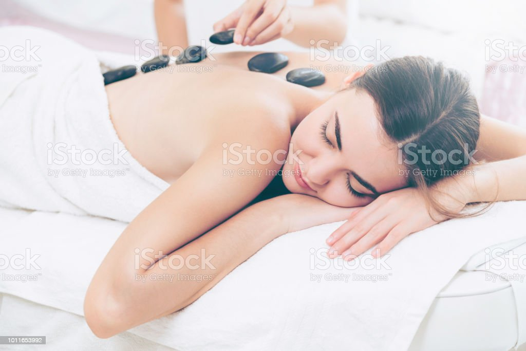 Hot stone massage treatment by therapist in spa. stock photo