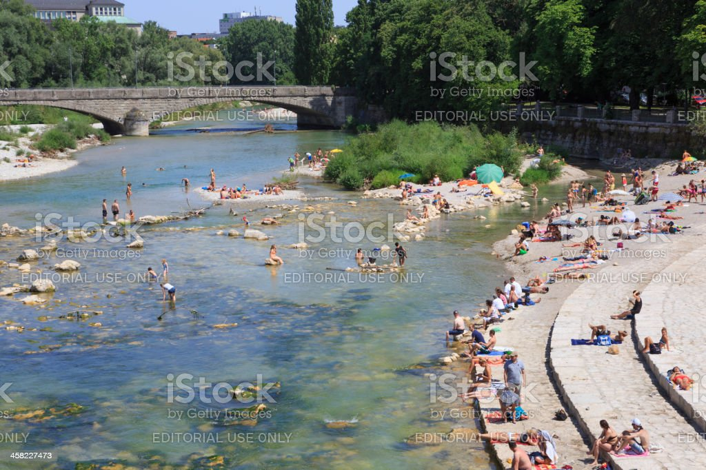 "Hot summer day at river Isar, Munich Munich, Germany - July 28, 2013: A hot summer day at river Isar in Munich. Several locals and tourists are enjoying the sun at the shore of lake Isar within Munich, Germany. In the background to the left the ""German Museum"" and the bridge Corneliusbruecke. Comfortable Stock Photo"