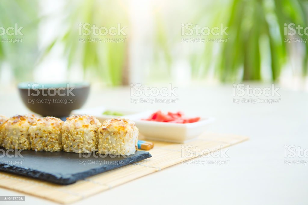 Hot sushi rolls served on black slate surface. Japanese food stock photo