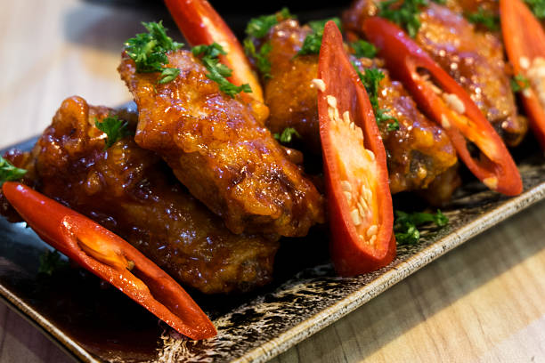 Hot sweet and spicy chicken fire with chilli stock photo