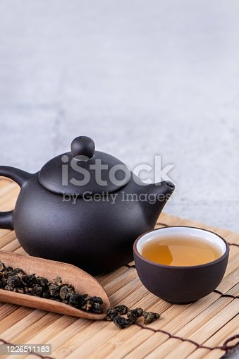 Hot tea in black teapot and cups and dry tea leaves over bright gray cement background, close up, copy space design concept.