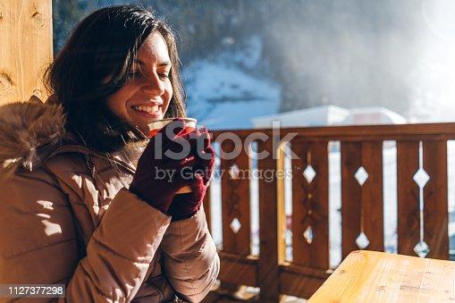 Young woman drinking tea in ski resort