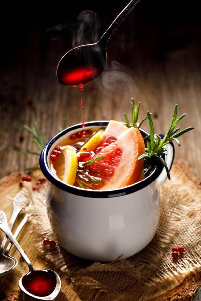 chaud l'infusion de thé au romarin, pamplemousse, citron, poivron rouge et jus de framboise dans une tasse d'émail sur un fond en bois - infusion pamplemousse photos et images de collection