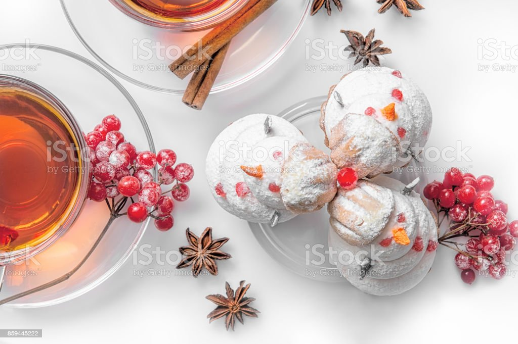 Hot tea on Christmas in glass transparent Cup with tea tree and cakes in the shape of snowmen out of meringue, cinnamon and vanilla.