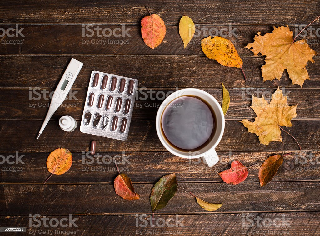 Hot tea, pills, thermometer and autumn leaves on rustic background. stock photo