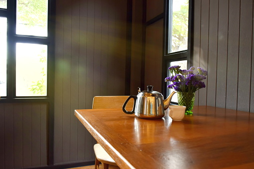 Hot tea pot with ceramic cup and vase of violet flowers on wooden table.Sunlight through the window into the room.