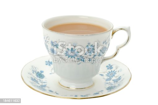 A cup of hot tea served in an ornate blue patterned bone china cup and saucer - studio shot.