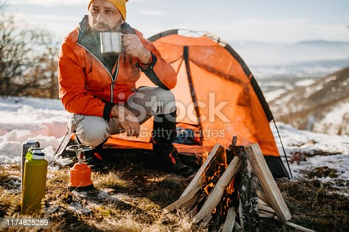 Mature man drinking hot drink in metal cup near tent on winter camping