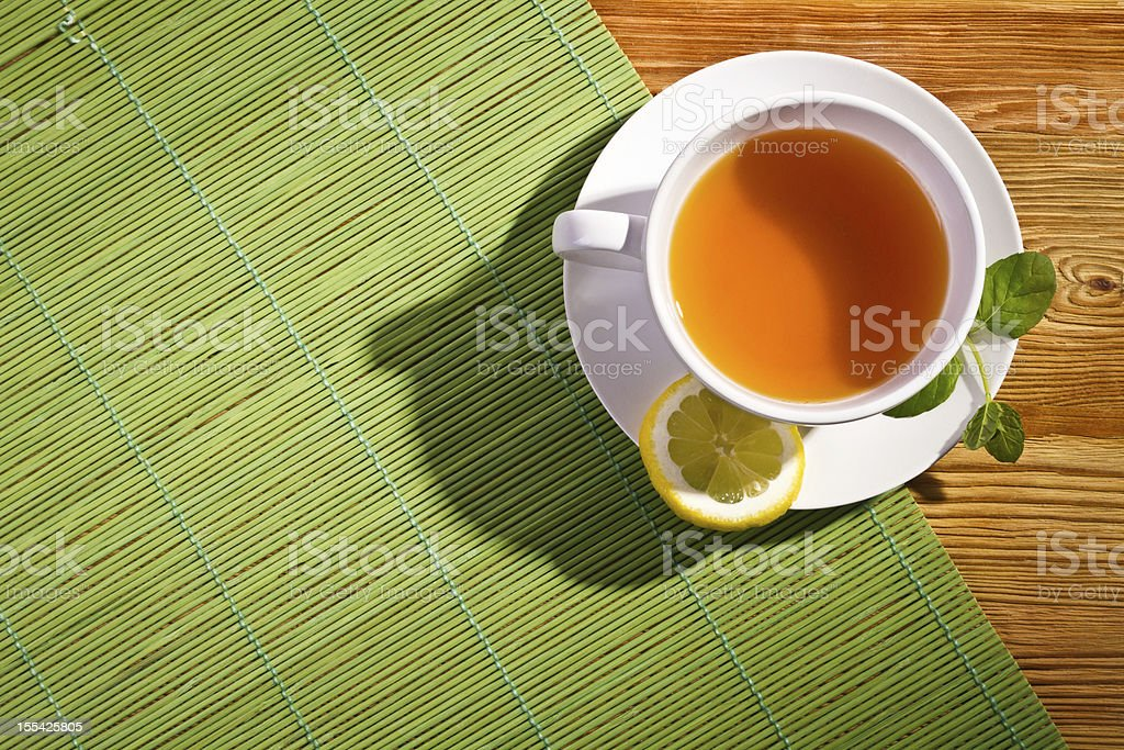 Hot tea with fresh leves and lemon on bamboo mat stock photo