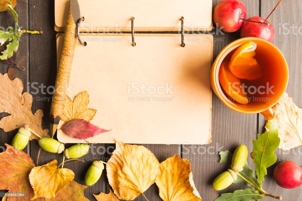 Hot tea with lemon, open notebook, autumn leaves on wooden background stock photo