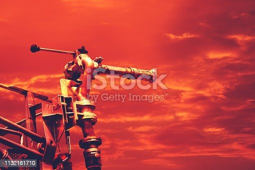 istock Hot temperature, firetruck water canon high pressure on dramatic red sky 1132161710