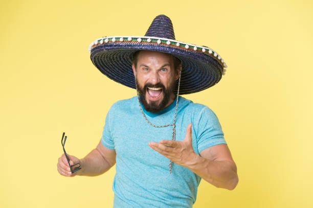 Hot tempered people. Man shouting face in sombrero hat yellow background. Guy with beard looks annoyed or angry in sombrero. Traditional rules of behaviour and manners. Man annoyed behaviour shout stock photo