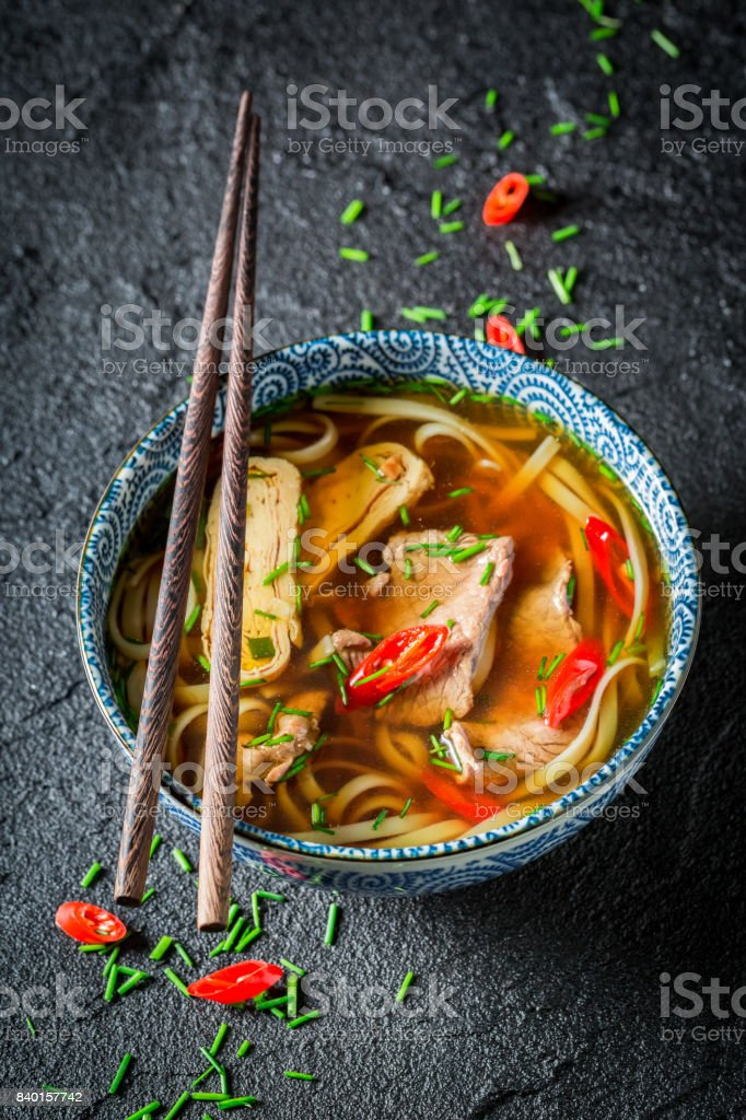 Hot Thai broth with beef and noodle on black rock stock photo