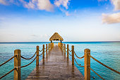 hot tropical day the Caribbean sea pier with pergola palm leaves