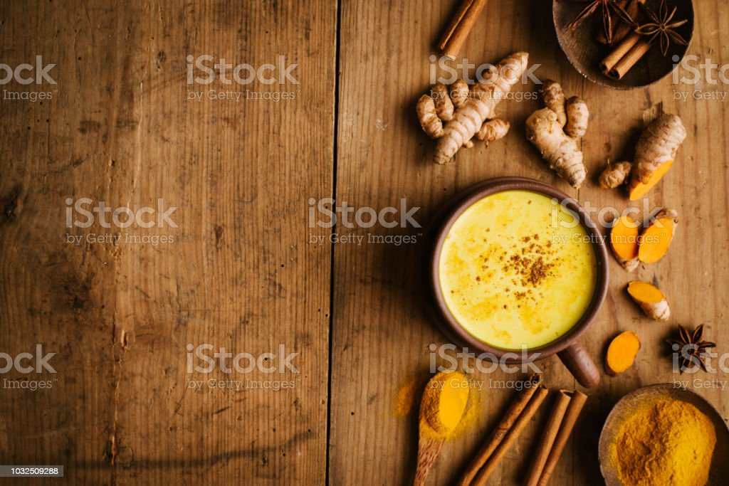 Hot turmeric milk with spices on wooden table stock photo
