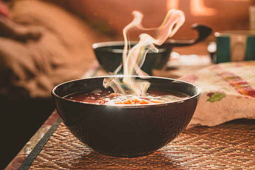 Hot vegetable soup in a dish made of natural materials. Traditional family lunch in a Russian village