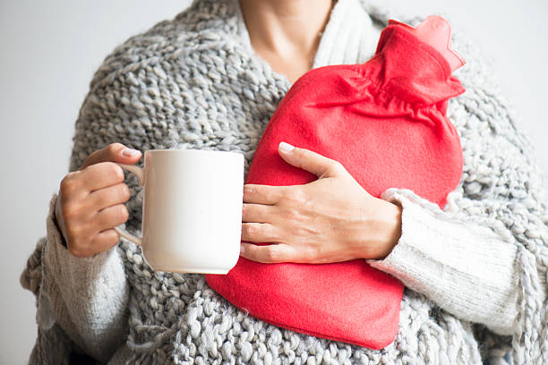 Hot Water Bottle and Cup of Tea Woman holding her hot water bottle and a hot drink. hot water bottle stock pictures, royalty-free photos & images
