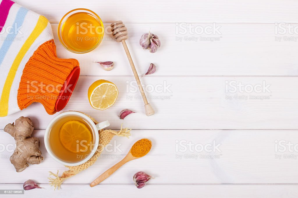 Hot water bottle, cup of tea, ingredients for preparation beverage stock photo