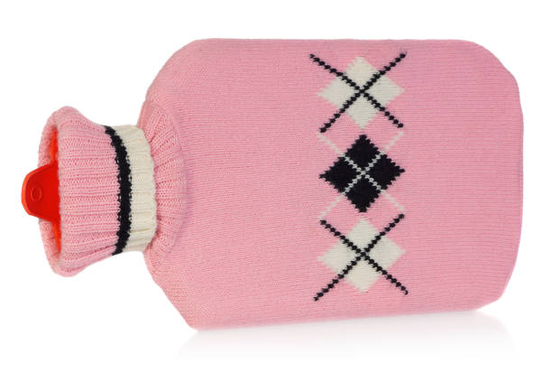 A hot water bottle in pink sweater with white and black patterns. A hot water bottle in pink sweater with white and black patterns. Heater isolated on white background with light shadow and reflection. hot water bottle stock pictures, royalty-free photos & images