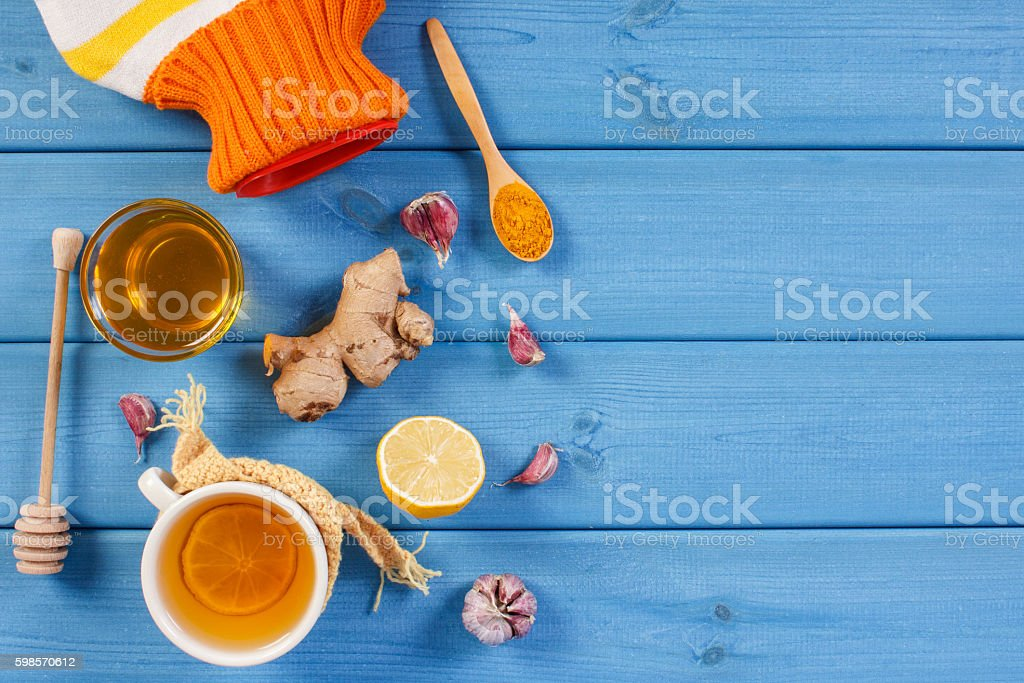 Hot water bottle, tea and ingredients for preparation warming beverage stock photo