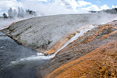Hot water from the midway basin flows into the firehole river in Yellowstone National Park.