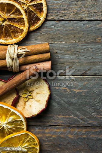 istock Hot winter holiday beverage aroma ingredients. Dried orange apple slices cinnamon sticks on old plank wood background. New year Christmas decoration elements. Vintage style copy space 1086790696