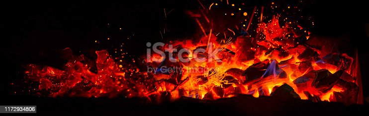 istock Hot wooden coals in the dark. Grill with hot coals and beautiful magic sparks with blue flame 1172934806