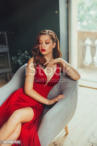172214590istockphoto Hot young adult and imperious woman, dressed in a long scarlet red long dress, sexually shows her nude elegant leg, sitting on a grey chair in a loft room with window to the floor, daring style 1077567830