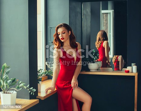 hot young adult, proud and domineering woman dressed in a long scarlet red long dress, sexually demonstrates her naked graceful leg, crouching on the window sill, room in loft stile with mirrors.