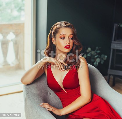 172214590istockphoto hot young adult, proud and imperious woman, dressed in a long scarlet red long dress, sexually holds her hand on her chest, sits on a grey chair in a loft room with window to the floor, cheeky style 1077567838