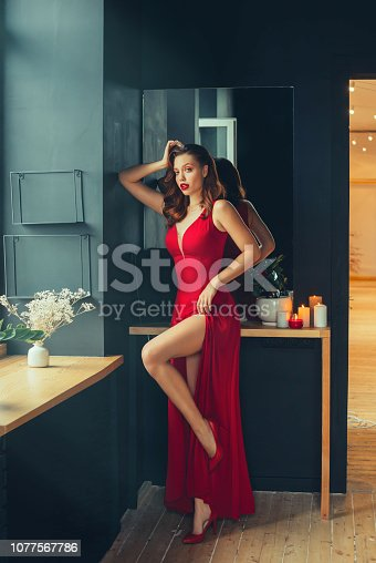 172214590istockphoto hot young adult proud woman wearing a long scarlet red long dress sexually demonstrates her naked graceful leg, standing on her heels with her back to the mirror in a modern room in loft style 1077567786