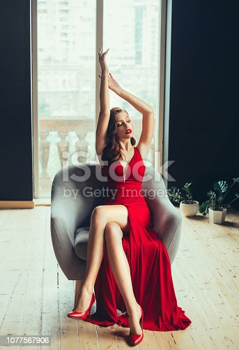 172214590istockphoto hot young proud woman, dressed in a long scarlet red long dress and red high-heeled shoes. Gently raises her hands up in a room with window to the floor in loft style. image for girls at graduation 1077567906