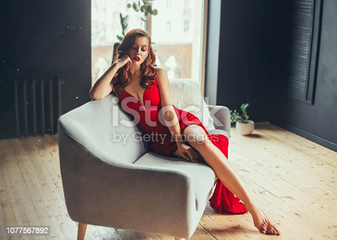 172214590istockphoto hot young woman, dressed in a long scarlet red long dress, sexually shows her bare legs sitting on a grey sofa in a loft modern room with window to the floor. Jessica rabbit halloween image 1077567892