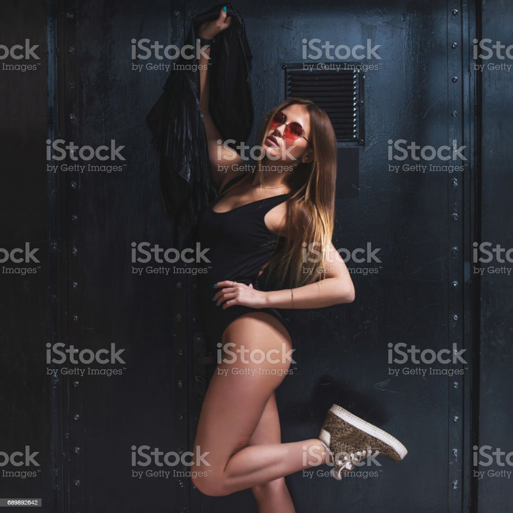 Hot young woman with perfect fit body posing in swimsuit and sunglasses holding a jacket against black background stock photo