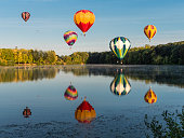 Albany, Oregon, USA - August 25, 2018: Hot-Air Balloons up in the air for the Northwest Art and Air Festival. They are over Freeway Lakes, a free Linn County public recreation area. The balloons are in flight with people in the wicker baskets. This free annual three-day Festival is held at Timber Linn Park, a city of Albany Oregon public park. It makes a great area for the Art sales booths, Music, food, Hot Air Balloon Launch area and more. The balloons Launch in the early mornings on Friday, Saturday and Sunday. This Saturday the balloons were floating to the South of Albany, near Freeway Lakes. The photo was taken from a public area.