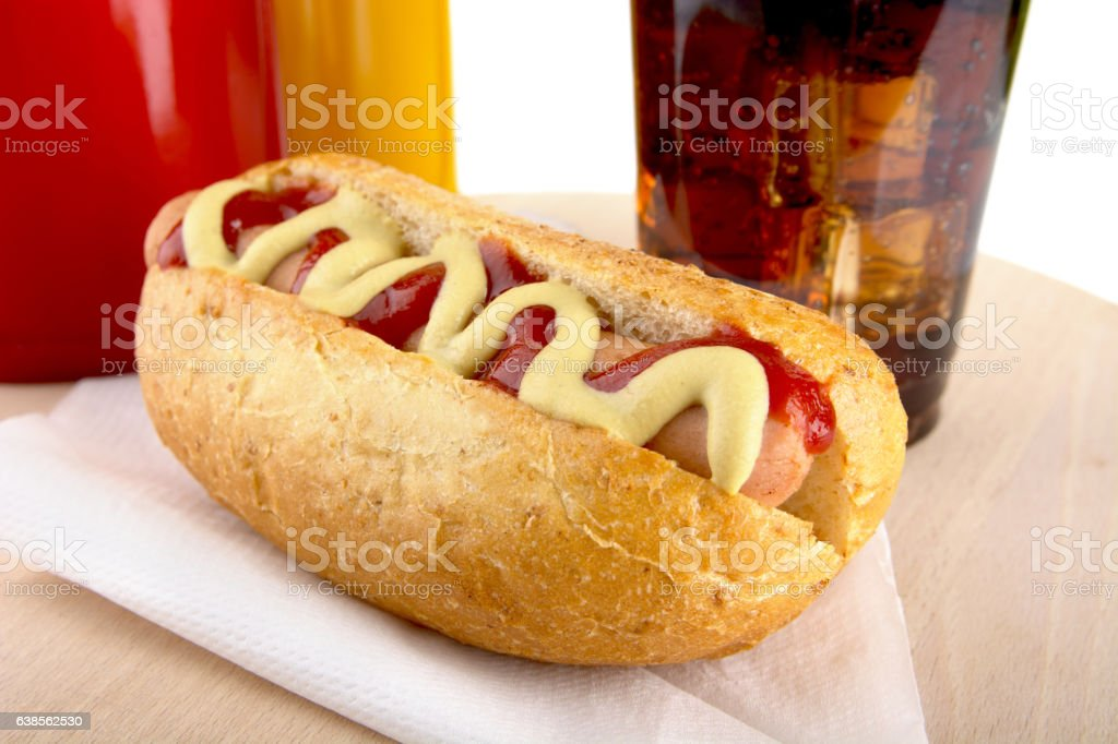 Hotdog with cola, bottle of mustard,ketchup on wooden desk stock photo
