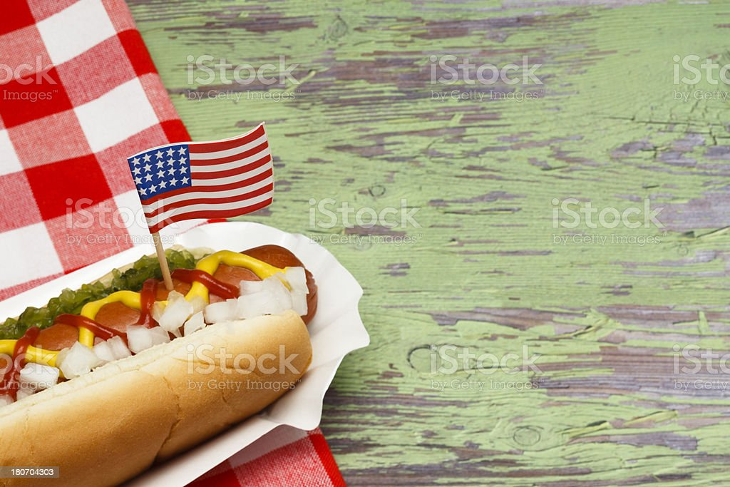 """Hotdog with Flag """"Ketchup, mustard, relish and onions on a hot dog with flag."""" American Culture Stock Photo"""