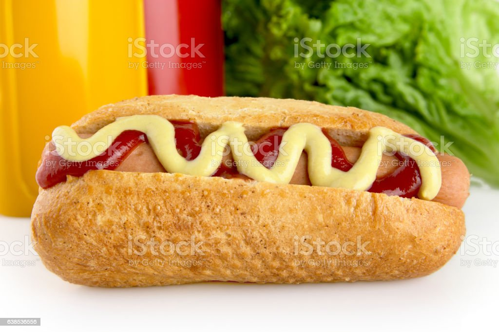 Hotdog with ketchup and mustard with salad in the background stock photo
