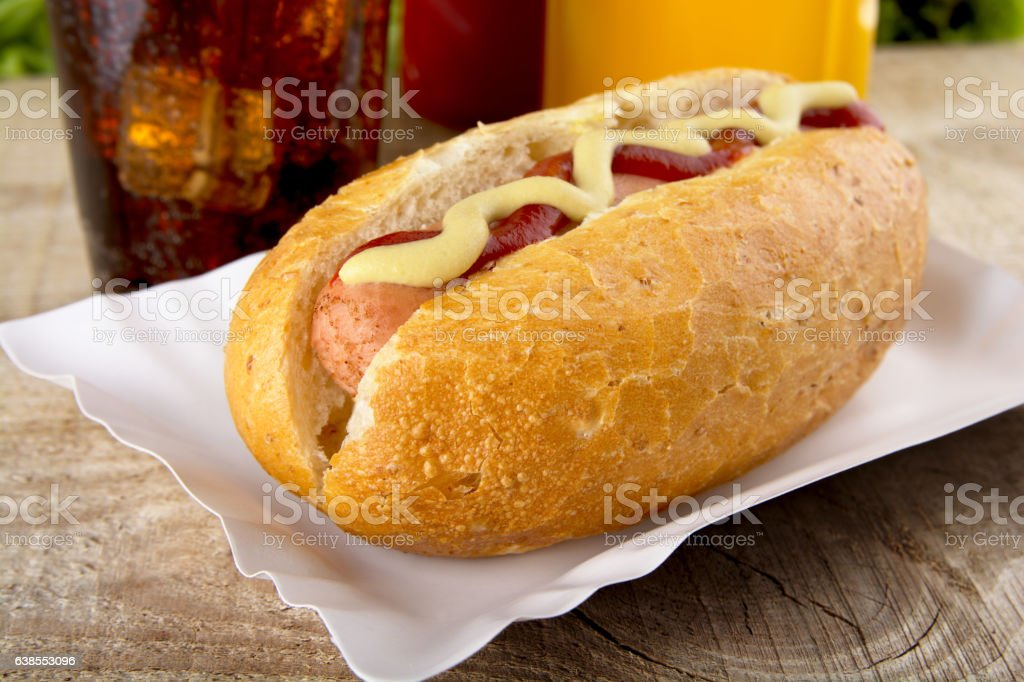 Hotdog with ketchup, mustard with cola on the wooden plank stock photo
