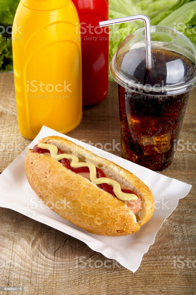 Hotdog with ketchup,mustard with cola on the wooden plank stock photo